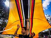 01 AUGUST 2017 - UBUD, BALI, INDONESIA: A kite flyer launches his bebean (fish shaped) kite on the public school soccer field in Ubud. Kite flying is a popular past time on Bali. It originally had religious connotations, it was used to ask the gods for bountiful rains and harvests. The kites are large. Small ones, flown by individuals are about two meters long, larger ones flown by teams of up to 80 people are ten meters long. There are three shapes of traditional kites, bebean (fish-shaped), janggan (bird-shaped) and pecukan (leaf-shaped). The pecukan is the most unstable and difficult to fly.    PHOTO BY JACK KURTZ