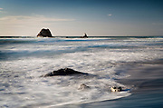water in motion, softened by capture, as it flows and crashes around the sea rocks at mangawhai, northland, new zealand