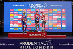 London, UK. 3 August, 2019. Elisa Balsamo (l, Valcar Cylance Cycling), Lorena Wiebes (c, Parkhotel Valkenburg) and Coryn Rivera (r, Team Sunweb) celebrate with champagne after finishing second, first and third respectively in the Prudential RideLondon Classique. The Classique, which is the richest one-day women's race in the world, covers 20 laps of a tight circuit of 3.4 kilometres around St James's Park and Constitution Hill.