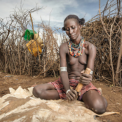 Village woman from Omo Valley cleaning a sking, Ethiiopia, Africa