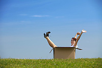 Cheerful young woman sitting in cardboard box at park with arms outstretched