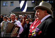 Parade marshall marches with accordionists during obby oss parade on May Day in Padstow; Cornwall, England.