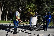 Wegwerkers spuiten teerasfalt voor nieuwe wegen, WK 2010 Zuid Afrika