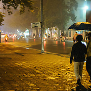 Two women with an umbrella to protect against the light rain, walk along the sidewalk of Ding Tien Hoang running along the side of Hoan Kiem Lake in Hanoi, Vietnam, at night.
