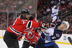 Jan 17; Newark, NJ, USA; New Jersey Devils defenseman Bryce Salvador (24) hits Winnipeg Jets center Alex Burmistrov (8) during the first period at the Prudential Center.