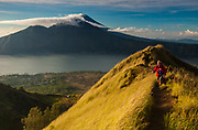 Tourist on hill top to watch dawn over Batur volcano and crater lake, Bali, Indonesia.