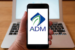 Using iPhone smartphone to display logo of ADM, Archer Daniels Midland, an American global food processing and commodities trading corporation