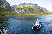Small tourist boat in mountainous fiord landscape, Raftsundet strait, Nordland, northern Norway