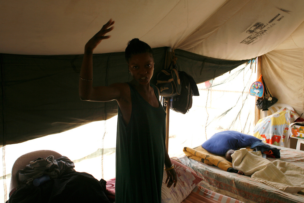 Agnes Sgmons 25 refugees from south Sudan in the tent that she sharing with other five woman and there children in the detention center in Qeziot, Israel..Monday November 12. 2007......Kalamin Charles Goda and Agnes Sgmons are a young couple that escaped the conflict in south Sudan region and sought refuge in Egypt in 2006...While the couple waited to have their refugee status processed, they struggled in Cairo. They received no financial assistance and were unable to work. Without a work permit, Agnes brought in about 300 Egyptian pounds a month (about $54). Desperate, the couple risked another dangerous move ? slipping across the border to Israel in the hopes they would gain their refugee status there and either stay and work in Israel or be relocated to the U.S...With the help of a Bedouin smuggler, the couple crossed the Sinai desert. Close to the border, they encountered Egyptian troops, who they say shot at them. Under fire, they ran for the Israeli border, having been told Israeli troops would protect them...Once in Israel, the couples were captured by an Israeli army patrol, who deposited them at a detention center in Qeziot, in southern Israel. Given hot food and clothing, Kalamin and Agnes were both interviewed by the UN, but were lodged in separate camps for men and women for several weeks before they saw each other again...During that time, doctors at a hospital in the Israeli city of Beer Sheva told Agnes she was four months pregnant. Kalamin had been given the news, but had not seen his wife for two weeks, since they arrived at the camp. Before leaving to meet her, he grabs a spare blanket, the only gift he can come up with to bring her...