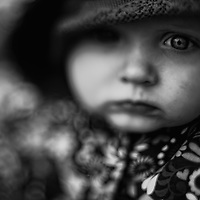 Close up of a baby in a patterned coat looking sad