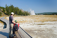 Couple watching Grand Geyser erupt, Yellowstone National Park