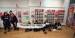 © under license to London News Pictures. 18/12/2010: Approximately 25 protesters picketed Top Shop and other shops associated with Philip Green, Vodafone and Boots to highlight corporate tax-avoidance. Protesters sat in Vodafone in Manchester's Arndale Centre and forced the shop to close for about an hour