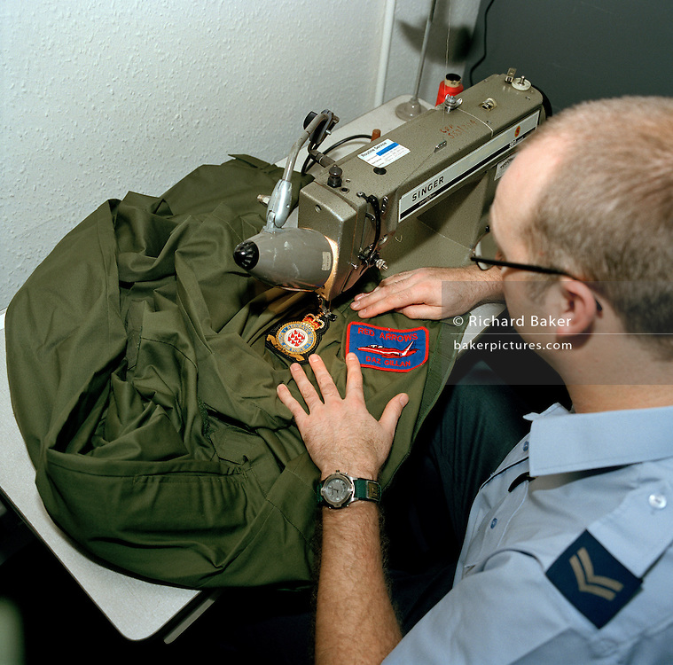 Safety equipment supplies officer of the Red Arrows, Britain's RAF aerobatic team sews on badges to working overalls.