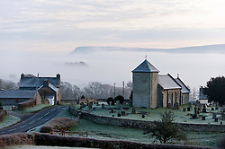 © Licensed to London News Pictures. 23/11/2015. Llanddewi'r Cwm, Powys, Wales, UK. St David's Church in the tiny Welsh hamlet of Llanddewi'r Cwm is surrounded by mist after a cold night with temperatures around freezing. Photo credit: Graham M. Lawrence/LNP