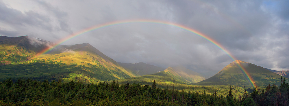 A vibrant rainbow spanning across a wide Alaskan mountain range.