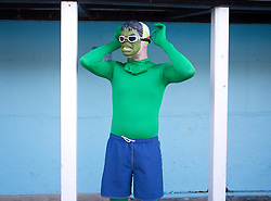 © Licensed to London News Pictures. 24/01/2015. London, UK. A contestant dressed up as The Incredible Hulk braves cold temperatures at the 6th UK Cold Water Swimming Championships at Tooting Bec Lido, south London. Over, 650 swimmers will take the plunge to compete in a variety of chilly races.  Photo credit : Isabel Infantes / LNP
