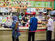 """11 DECEMBER 2018 - SINGAPORE: People lined up a food shop in a """"hawker court"""" in the Geylang neighborhood. Singapore forced food venders off the street and put them in hawker courts years ago. The Geylang area of Singapore, between the Central Business District and Changi Airport, was originally coconut plantations and Malay villages. During Singapore's boom the coconut plantations and other farms were pushed out and now the area is a working class community of Malay, Indian and Chinese people. In the 2000s, developers started gentrifying Geylang and new housing estate developments were built.    PHOTO BY JACK KURTZ"""