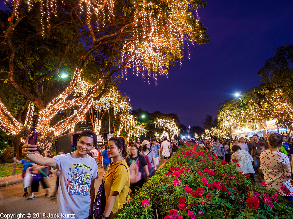 24 NOVEMBER 2018 - BANGKOK, THAILAND:  A couple takes a selfie at the Red Cross Fair in Lumpini Park. The Red Cross Fair is a fund raiser and annual event in Bangkok that draws thousands of attendees every night of its nine day run. The fair features games of chance, a midway with rides, handicrafts and food. This is the first year the fair has been in Lumpini Park. Previously it had been held in the Dusit section of Bangkok. The 2018 Fair marks 125 years of service for the Red Cross in Thailand.    PHOTO BY JACK KURTZ