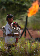 The Kichwas tribe, Elvia Chimbo Aquinda and her son Rivaldo Aquida 1, walk though a remediated oil field in the backgound gas is burnt off from a nearby oil field. Elvia is the daughter of Maria Aquinda whom the lawsuit against the oil companies is named after. Picture taken in Rumipamba, Sucumbios region of Ecuador, Sunday, October 26, 2003.