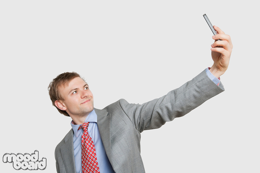 Handsome young businessman taking self-portrait photograph over colored background