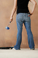 Woman painting wall with paint roller low section back view