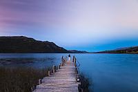 HOMBRE EN UN MUELLE DEL LAGO PELLEGRINI AL ANOCHECER, CHOLILA, PROVINCIA DEL CHUBUT, ARGENTINA (PHOTO © MARCO GUOLI - ALL RIGHTS RESERVED)