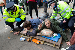 © Licensed to London News Pictures. 09/10/2019. London, UK. Police begin to remove two glued on Extinction Rebellion protesters from a roadblock on Horse Guards Road. Police continue to attempt to clear roads in Westminster on the third day of the protest.  Photo credit: George Cracknell Wright/LNP