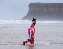 © Licensed to London News Pictures. <br /> 01/01/2017. <br /> Saltburn by the Sea, UK.  <br /> <br /> A woman wearing a onesie walks from the cold waters of the North sea as she takes part in the annual New Year Day dip at Saltburn beach.<br /> <br /> The event helps to raise money for the Saltburn Animal Rescue Association.<br /> <br /> Photo credit: Ian Forsyth/LNP