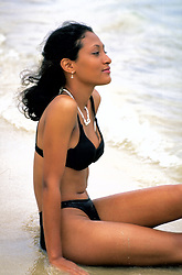 An attractive young woman relaxes on the beach on the island of Jamaica.