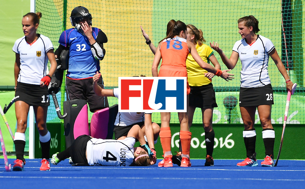 Germany's Nike Lorenz (bottom) lies on the pitch after resulting injuried during the women's semifinal field hockey Netherlands vs Germany match of the Rio 2016 Olympics Games at the Olympic Hockey Centre in Rio de Janeiro on August 17, 2016. / AFP / Pascal GUYOT        (Photo credit should read PASCAL GUYOT/AFP/Getty Images)