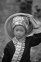 A young Flower Hmong girl carrying her wash basin
