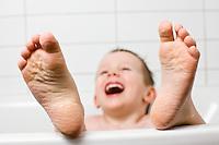 Ari Carl í baði heima í Sandavaði. Skellihlæjandi, tærnar í forgrunni. Young boy laughing while taking his bath. Toes in foreground.