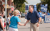 Marching along Main Street during the July 4th parade Mitt Romney shakes hands with Kathie Brown of Laconia on Monday afternoon.  (Karen Bobotas/for the Laconia Daily Sun)