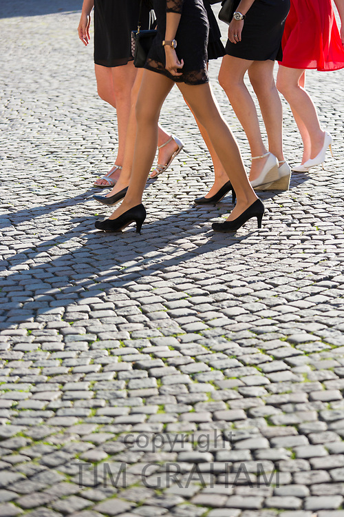 Girls' night out - bare legs, high heels and miniskirts short skirts of young ladies in hen party girl power group on cobble stones in Bruges, Belgium