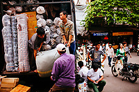 Workers unload a truck of goods at Dong Xuan market in Hanoi, Vietnam.