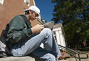 18386.Jason Sharp reads The Post between classes Thursday near Shively Hall.(photo by Kevin Riddell)