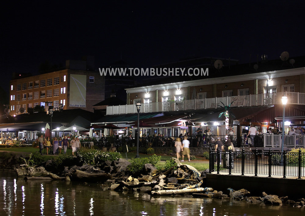Newburgh, New York - People walk on the sidewalk on the Hudson River waterfront as others crowd the bars and restaurants in the background on the evening of June 15, 2011.
