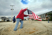 Belmar resident Diane Ragickas plants an American flag into the storm ravaged beachfront in Belmar two days after Hurricane Sandy made it's way through the area on October 31. Hurricane Sandy forced the shutdown of mass transit, schools and financial markets, sending coastal residents fleeing for higher ground, and threatened a dangerous mix of high winds and soaking rain.