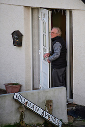 © Licensed to London News Pictures. 13/01/2017. Jaywick, UK. A man stands at the front of his home looking out over the sea, on the seafront at Jaywick where homes were expected to evacuated due to the threat of flooding in low-lying areas . Photo credit: Ben Cawthra/LNP