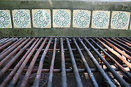 Detail of a grill with green ceramic tiles. <br />
