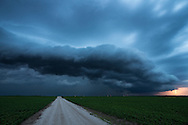 A shelf cloud approaches a field of soybeans near Delavan, IL. The late evening light made the clouds a cool blue while the lightning caused a warm glow.<br />