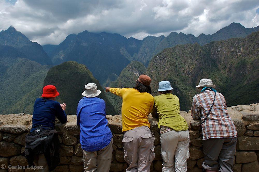 A guide is pointing to the left sidde of the ruins of machu picchu in Cusco, Peru.