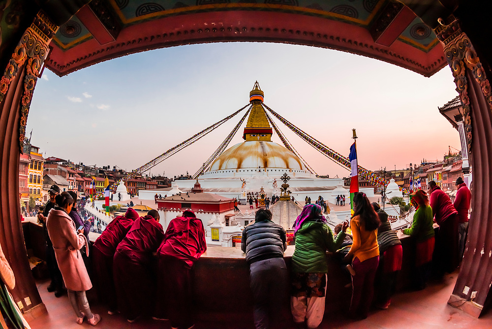Tibetan monks and pilgrims stand on the balcony of the Guru Lhakhang Monastery overlooking the Boudhanath Temple. It is the largest stupa in Nepal and the holiest Tibetan Buddhist temple outside Tibet. It is the center of Tibetan culture in Kathmandu, Nepal.