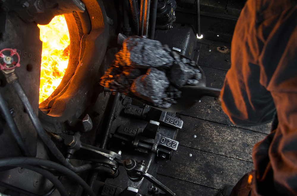 "The ""Fireman"" feeds coal into the steam powered locomotive's furnace."