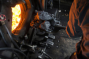 "The ""Fireman"" feeds coal into the steam powered locomotive's furnace."