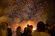 Fireworks are thrown into a bonfire society tar barrel at the late night parades in Lewes.