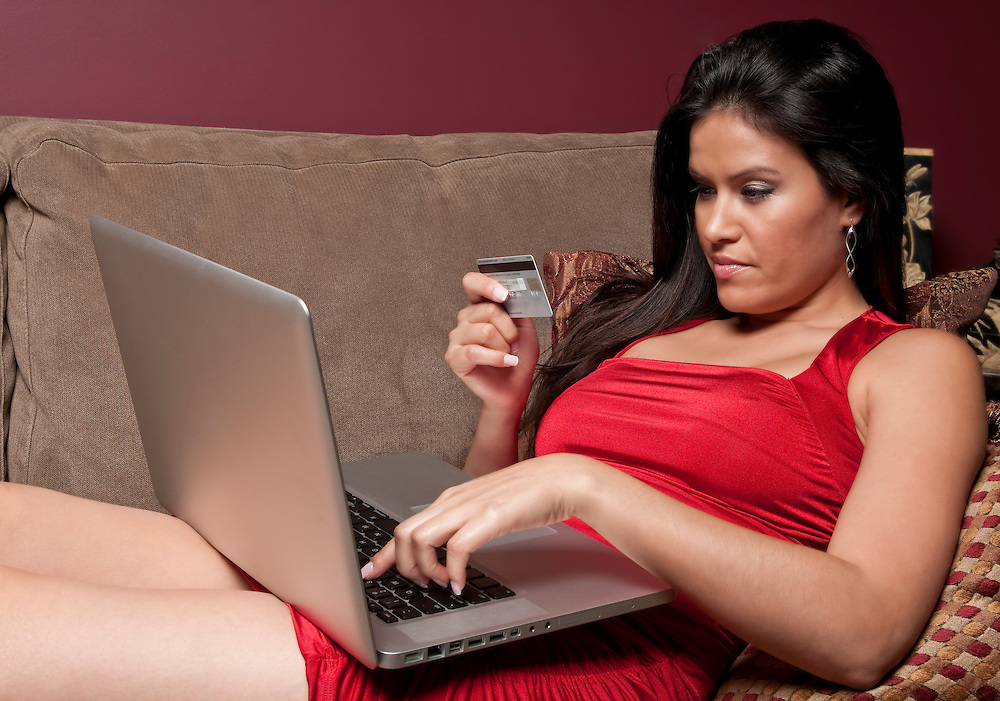 Young hispanic woman shops online from the comfort of her sofa.