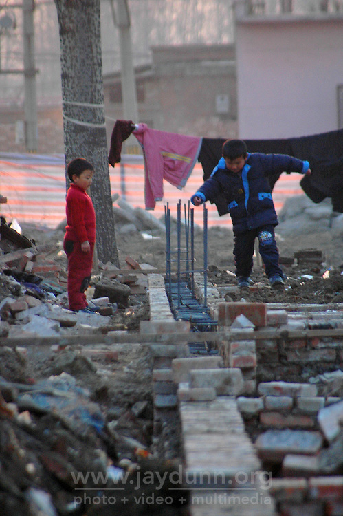 China, Beijing, Ping Fang Xiang, 2008. Children play right in the middle of one of Ping Fang Xiang's numerous construction sites. This project is utilizing recycled bricks to improve local housing..