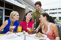 Waiter Bringing Check to Women in Restaurant
