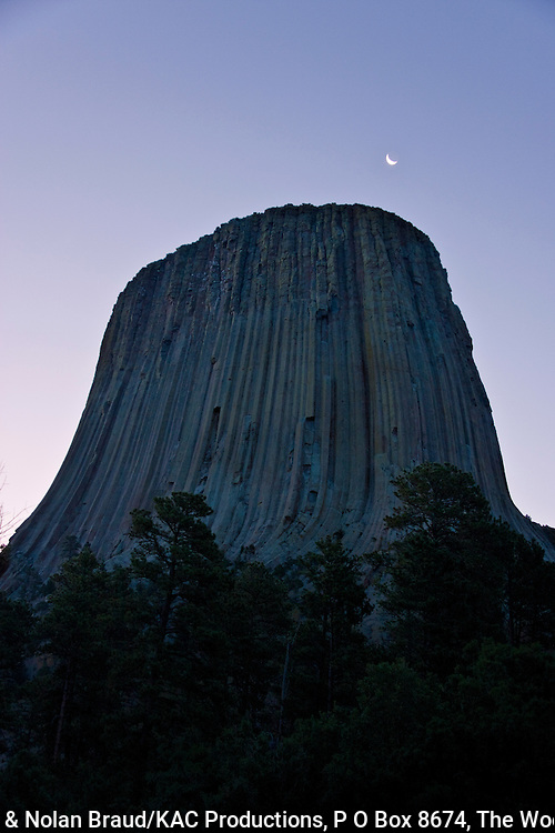 Moon over Devil's Tower National Monument in Wyoming just before sunrise.